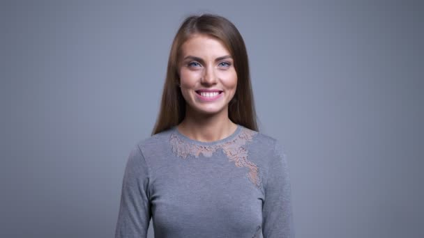Closeup portrait of positive beautiful caucasian woman looking straight at camera and smiling