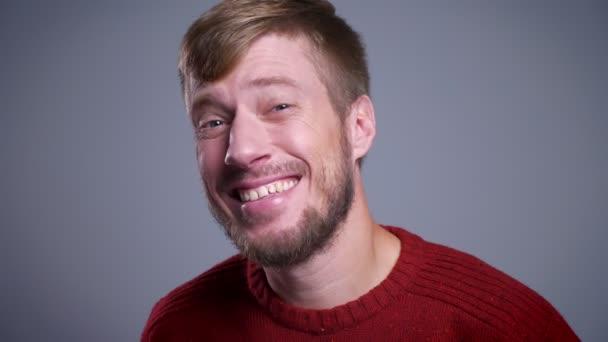 Detailní portrét šťastný muž středního věku kavkazské při pohledu na fotoaparát a usmívá se na pozadí izolované na šedé