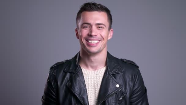 Vértes portréja vonzó fiatal férfi keres, egyenesen a kamera, és mosolyogva