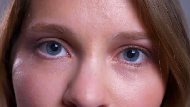 Detailní záběr na krásné mladé Kavkazský žena modré oči díval přímo do kamery s neutrálním výrazem obličeje