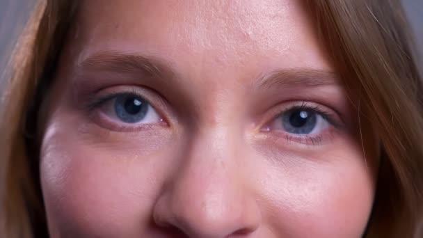 Vértes bájos fiatal kaukázusi nő kék szeme néz egyenesen a kamera a boldog arc kifejezése