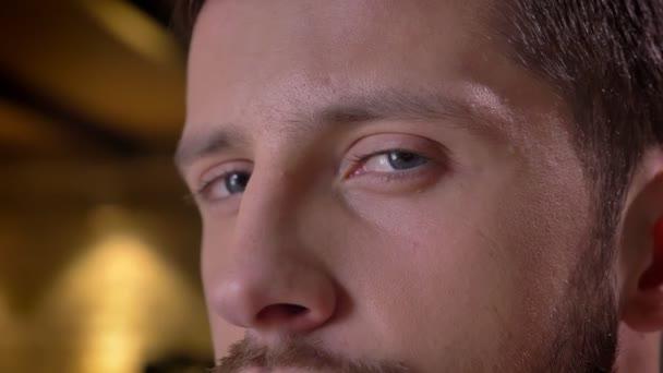 Detailní portrét mladého kavkazské mužské tváře s modrýma očima, těší a pak na kameru s úsměvem