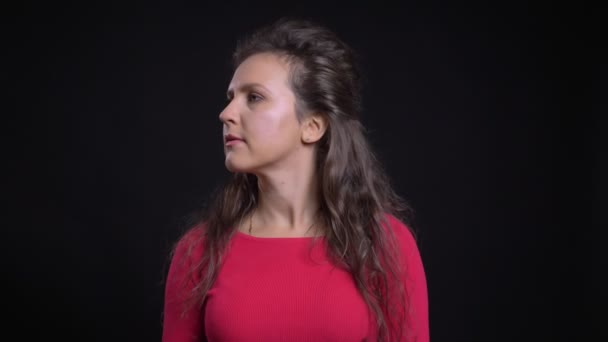 Portrét kavkazské ženy v červené barvě ji otočí hlavu a klidně díval do kamery na černém pozadí.