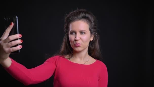 Portrét kavkazské ženy v červené barvě s úsměvem fotí selfie pomocí smartphone na černém pozadí.