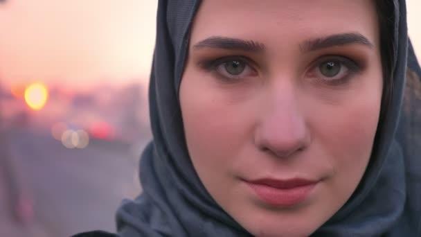 Nahaufnahme Porträt einer jungen attraktiven muslimischen Frau im Hijab-Gesicht, die selbstbewusst in die Kamera blickt und die Stadt auf dem Rücken trägt