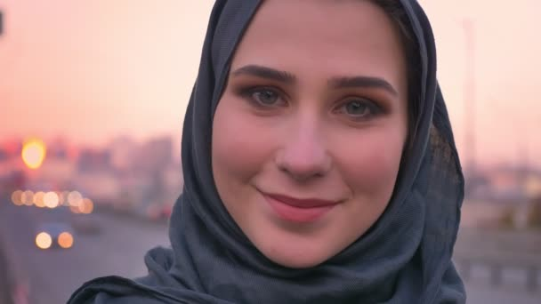 Closeup portrait of young attractive muslim woman in hijab smiling and looking at camera with the urban city on the background