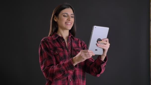 Portrét mladé a krásné kavkazské dlouhé vlasy-děvče stydlivě usmívat do tabletu na černém pozadí
