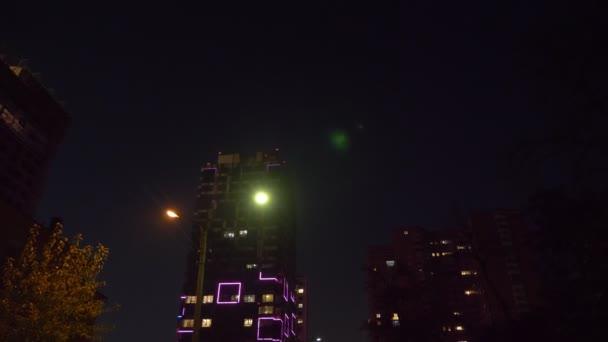 Csúsztassa a lövés a város épületeit, lassan mozgó háttér fekete éjszakai fények.