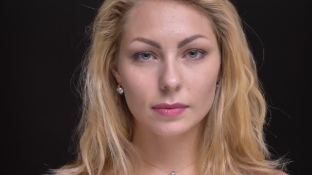 Nahaufnahme Porträt der wunderschönen kaukasischen langhaarigen Frau, die ruhig in die Kamera auf schwarzem Hintergrund schaut.