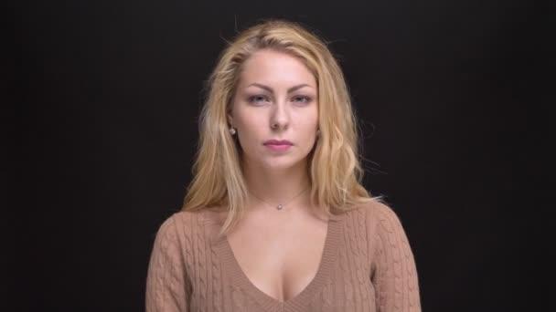 Portrét krásné kavkazské dlouhé vlasy-ženy negativně kroucení hlavou do kamery na černém pozadí.