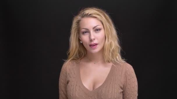 Portrét radostné kavkazské dlouhé vlasy ženy flirtingly třásl její vlasy do kamery na černém pozadí.