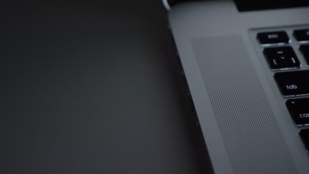 Close-up shot mužské ruky fastly vložením usb kabel do notebooku na pozadí černý stůl