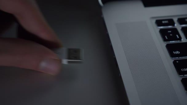 Close-up shot mužské ruky fastly vkládání kabelu usb do notebooku na pozadí černý stůl