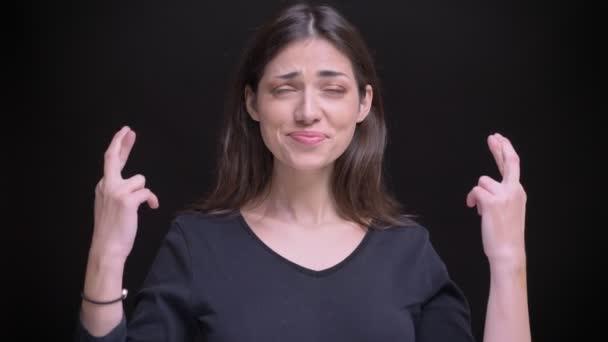 Portrét radostné kavkazské dlouhé vlasy brunetka ukázal překřížené prsty znamení doufat v co na černém pozadí