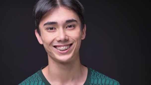 Nahaufnahme Porträt des jungen fröhlichen koreanischen männlichen Gesichts, das direkt in die Kamera schaut und glücklich lächelt