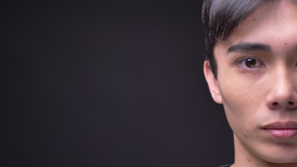 Closeup poloobličejových portrét mladé atraktivní korejský mužská tvář hledí přímo na kameru s pozadím izolované na šedé