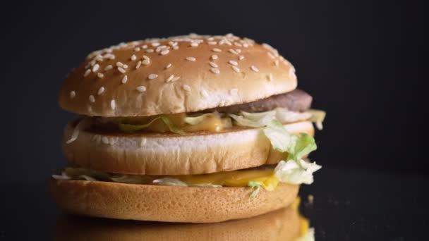 Closeup střílet ze šťavnaté dvojitý cheeseburger s hlávkovým salátem chutné karbanátky a sezam na buchty