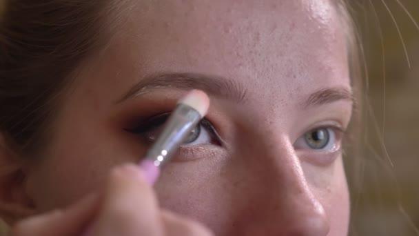 Vértes portré fiatal kaukázusi nő sminkes alkalmazása a fehér eyedhadows, a szemöldök felett lenyűgöző barna füstös szemek megjelenés alatt