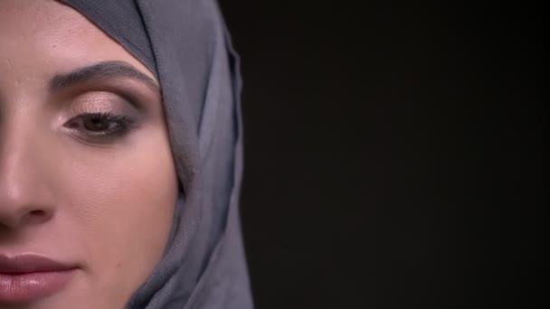 Detail napůl portrét krásné muslimské ženy v hidžábu s světlý make-up usmívat radostí do kamery na černém pozadí.