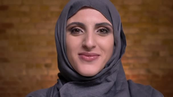 Portrait of beautiful muslim woman in hijab with bright make-up shyly turning her head and smiling into camera on bricken wall background.