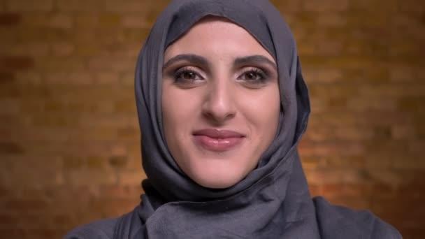 Portrét krásné muslimské ženy v hidžábu s světlý make-up stydlivě odvrátila hlavu a s úsměvem do kamery na zeď bricken na pozadí