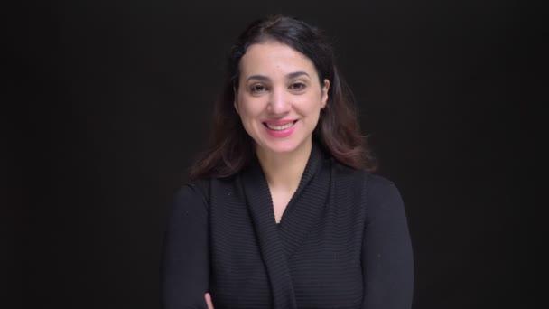 Nahaufnahme Porträt einer erwachsenen attraktiven kaukasischen Frau, die lacht, während sie mit den Armen über der Brust in die Kamera blickt