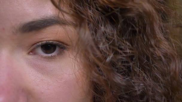 Vértes fél arcát portré fiatal vonzó kaukázusi női arc, barna szemmel nézett egyenesen a kamera