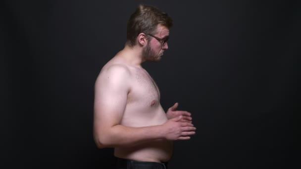Portrét v profilu nahou obézní mladík smutně díval do kamery a dotýká břicho na černém pozadí.