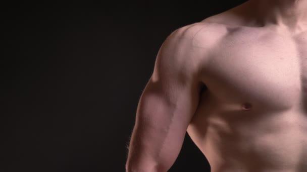 Közelkép álló férfi izmos bicepsz és a mell, a fekete háttér.