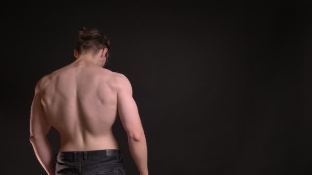 Rückporträt eines jungen kaukasischen Mannes, der seinen muskulösen Bizeps auf schwarzem Hintergrund zeigt.