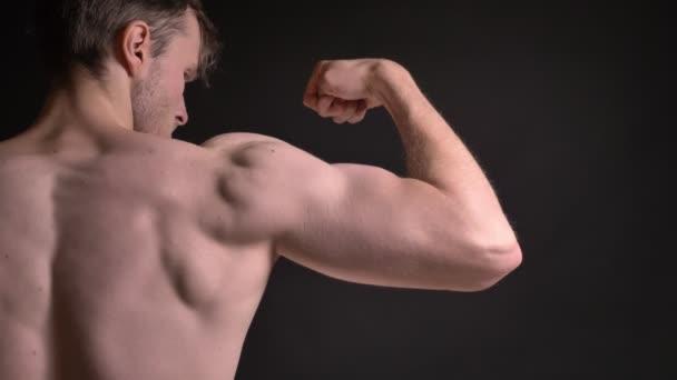 Detail zadní portrét mladíka kavkazské ukazující jeho svalnaté biceps a demonstrovat svou moc na černém pozadí.