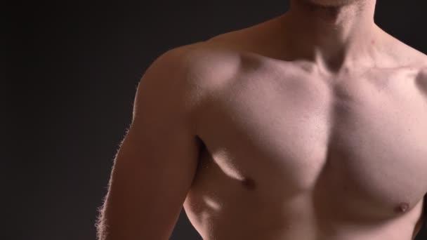 Detail portrét kavkazské svalové prsu mužského na černém pozadí.