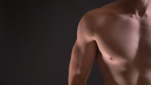 Detail napůl portrét kavkazské svalové prsu mužského s kapky vody na nich na černém pozadí