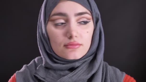 Portrait of attractive muslim woman in hijab with one eye-arrow turning her head showing make-up to camera on black background.