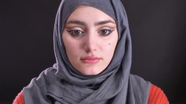 Portrait of beautiful muslim woman in hijab with bright make-up watching seriously into camera on black background.