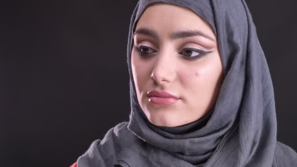 Portrait in profile of beautiful muslim woman in hijab with fashionable make-up turns to camera and watches calmly on black background.