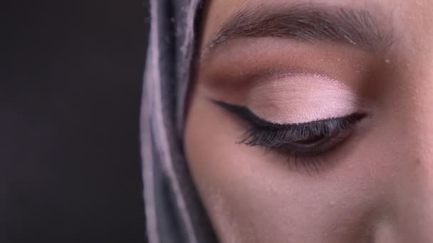Close-up half-portrait of young muslim woman in hijab with fashionable make-up watching downwards on black background.