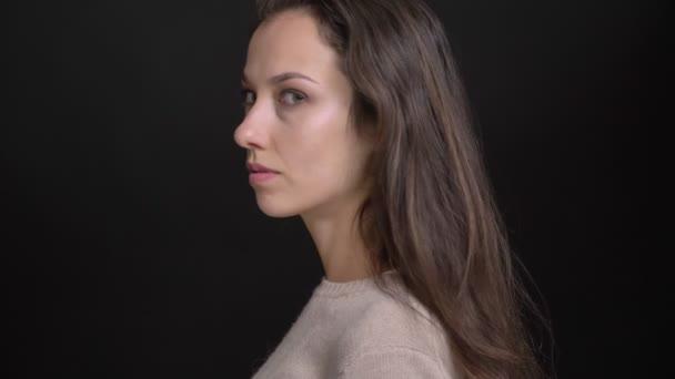Közeli kép: portré, fiatal barna lány, kaukázusi kamera fordul, és órák komolyan bele a fekete háttér.