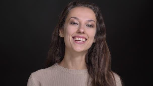 Portrét detail brunetka dlouhé vlasy-kavkazský dívky s úsměvem dívat do kamery na černém pozadí.