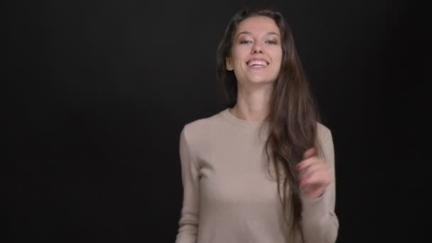 Close-up portrait of brunette long-haired caucasian girl smilingly dancing to music on black background.