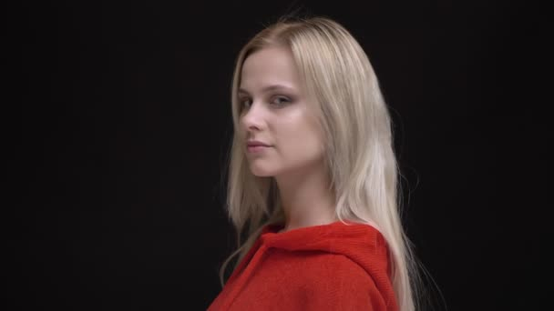 Portrait of young white-haired caucasian girl in red sweater turns to camera and watches calmly into camera on black background.