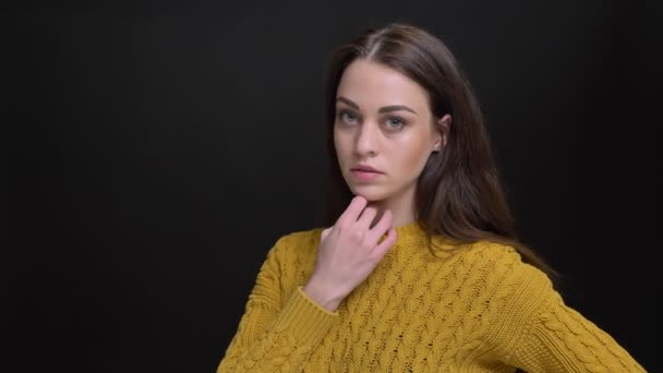 Portrait of long-haired brunette girl in yellow sweater slowly posing into camera on black background