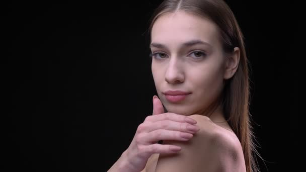 Portrait in profile of slim caucasian girl with nude make-up slowly touching her shoulder and collarbone on black background.