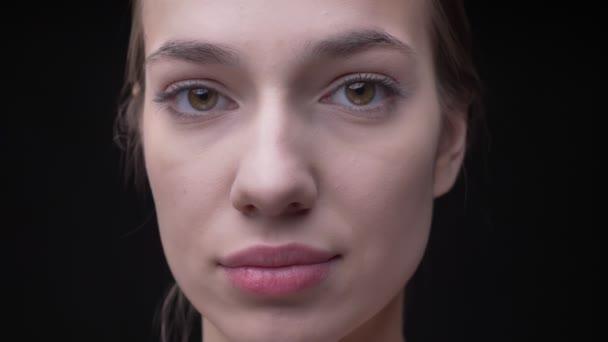 Fiatal, vékony kaukázusi lány nyugodtan figyelte a fekete háttér kamera nude make-up közeli portréja.