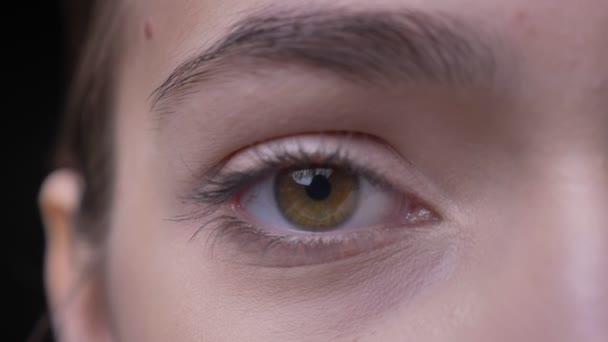 Detail napůl portrét mladé kavkazský dívky s nahé líčení očí a vážně hodinek do kamery na černém pozadí.