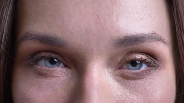 Vértes portréja kaukázusi felnőtt női arc, kék szemmel nézett egyenesen a kamera