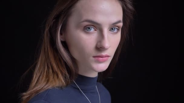 Close-up portrait of young and slim brunette caucasian girl turns to camera and watches calmly into it on black background.