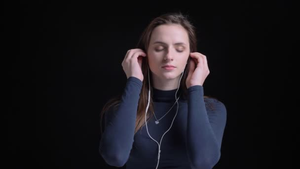 Portrait of young and slim brunette caucasian girl listening to music in earphones and dancing with satisfaction on black background.