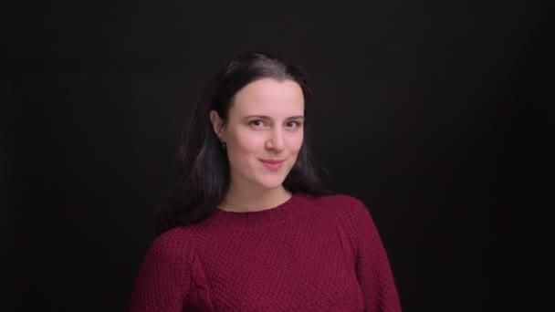 Closeup Portrait von junge hübsche kaukasischen Frau mit schwarzem Haar verführerisch Lächelnd zwinkerte und ihre Lippen beißen, während der Blick in die Kamera