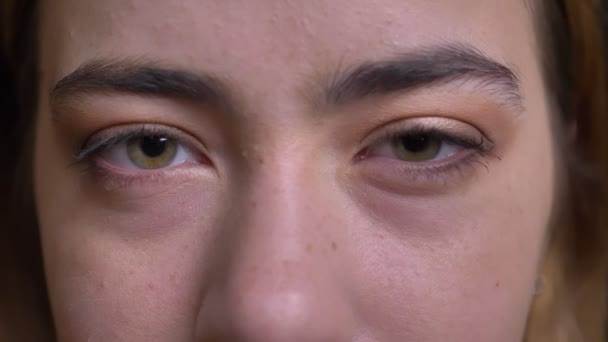 Detailní portrét mladé krásné kavkazské ženské tváře se zelenýma očima zíral přímo na kameru s unavený vzhled